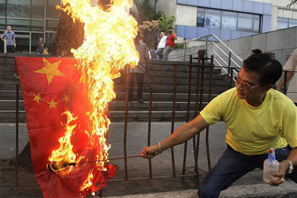 A protester burns a Chinese flag outside the Chinese consulate in suburban Makati, south of Manila, Philippines Tuesday, May 8, 2012. The Philippines and China are in a standoff over Scarborough Shoal which began early April after the Philippine navy accused Chinese boats of illegally fishing in the area. The Philippines says the shoal lies within its exclusive economic zone.(AP Photo/Aaron Favila)